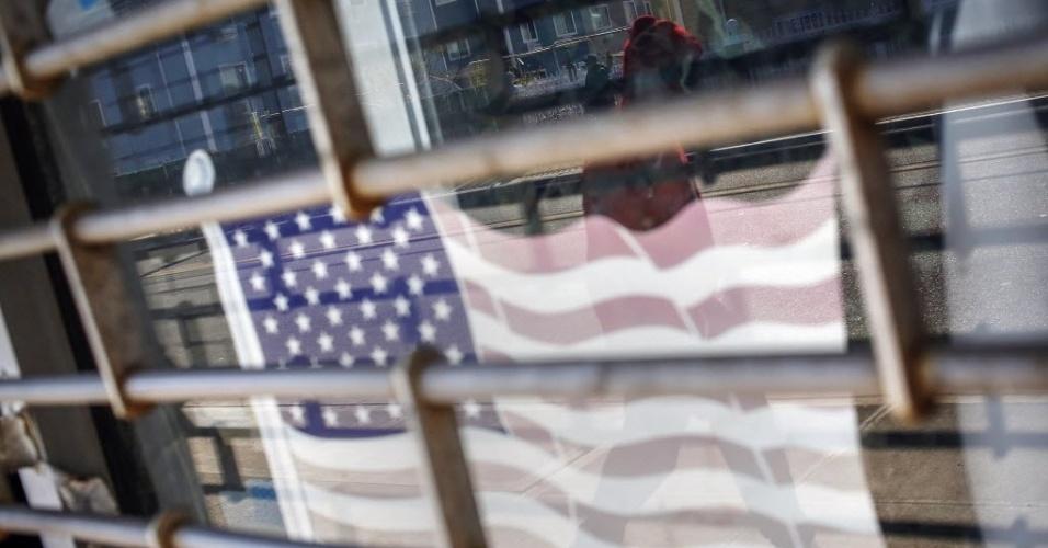 29.out.2013 - Pessoa passa nesta terça-feira (29) em frente a loja fechada desde a passagem do furacão Sandy por Nova York. A passagem da supertempestade que matou pelo menos 159 pessoas, danificou mais de 650 mil casas, e trouxe prejuízos estimados em US$ 70 bilhões para o país, completa um ano nesta terça-feira