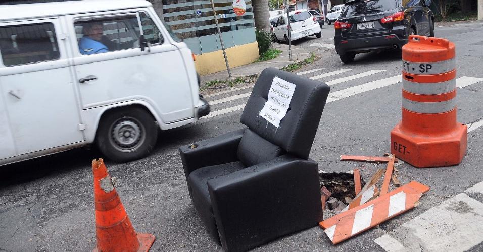30.out.2013 -  Uma poltrona com cartaz com a frase 'Sentados, esperando a prefeitura tapar o buraco' é colocada para tapar buraco na rua Cabo Verde, no Itaim Bibi, em São Paulo, nesta quarta-feira (30)
