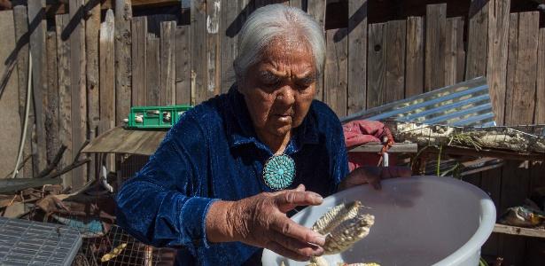 Nora Kaibetoney junta pedaços de milho seco para preparar prato típico dos navajo. Ela está entre os índios de sua etnia que buscam alento na Igreja Mórmon em tempos de desespero