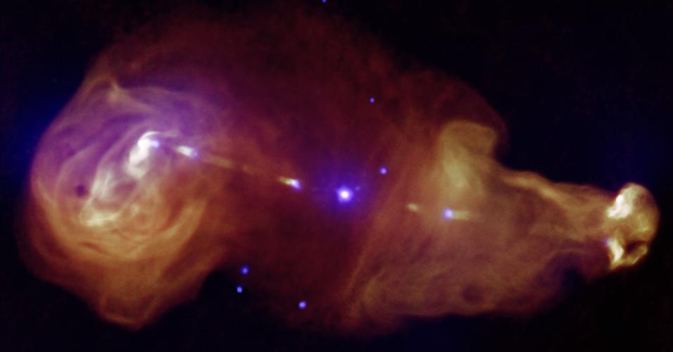 1º.nov.2013 - Buracos negros supermassivos que ficam no centro das galáxias soltam jatos com grandes quantidades de energia, como ocorre com o 3C353. Essa grande fonte de energia encobre a galáxia (ponto brilhante no centro da imagem) com plumas gigantes de radiação - a sombra roxa é a observação feita em raios x do Observatório Chandra, enquanto a mancha laranja representa os dados de rádio do telescópio Very Large Array, indica a Nasa (Agência Espacial Norte-Americana)