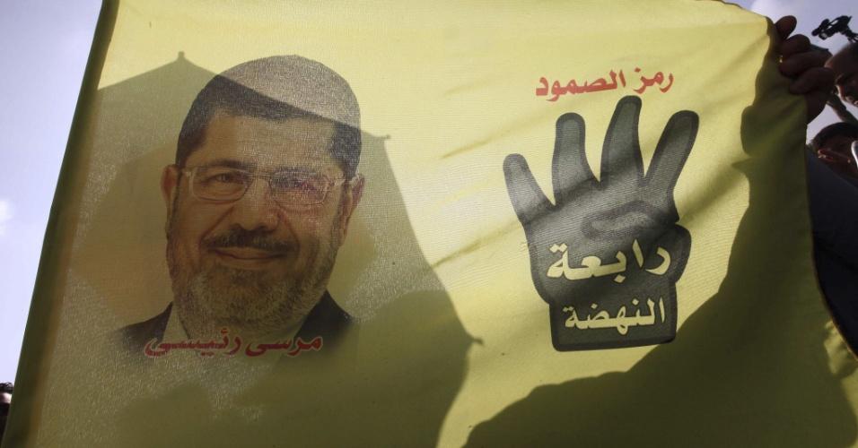 4.nov.2013 - Bandeira em apoio a Mohamed Mursi, que foi deposto da presidência do Egito, é hasteada do lado de fora de uma academia de polícia no Cairo, onde Mursi está sendo julgado