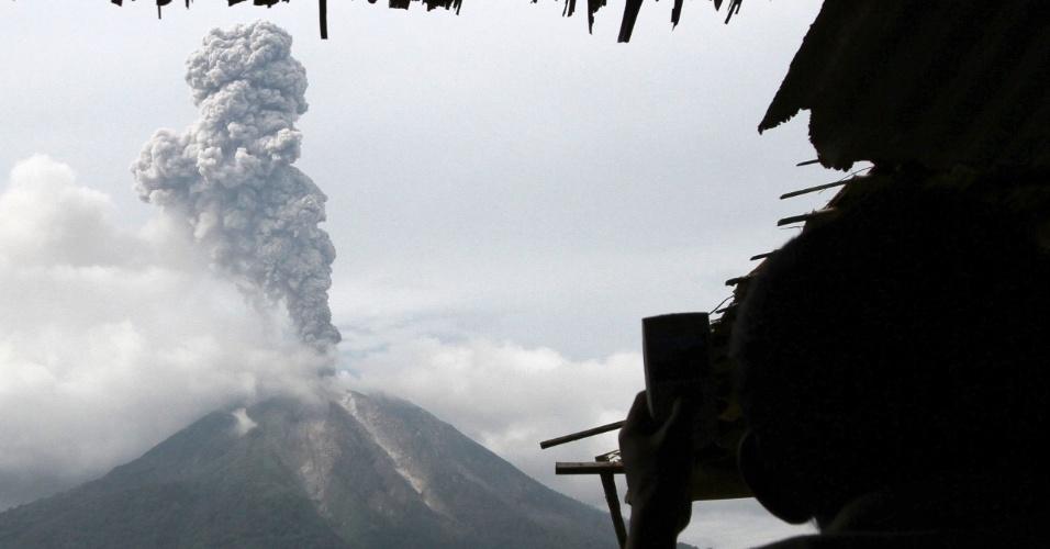 5.nov.2013 - Morador de vila em Karo, na Indonésia, fotografa erupção do Monte Sinagung nesta terça-feira (5). O vulcão está em erupção desde o último domingo (3)