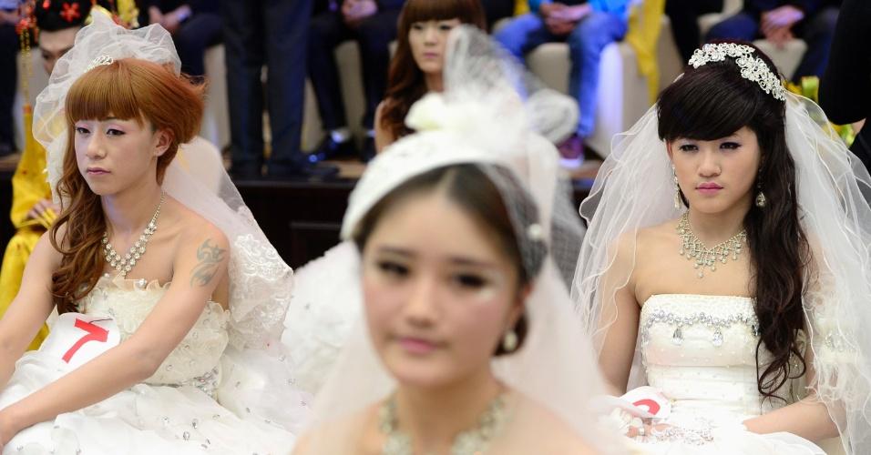 7.nov.2013 - Homens com vestidos de noiva participam de concurso de maquiagem em Jinan, na província de Shandong (China), nesta quarta-feira (6). Cada participante do concurso de maquiagem recebe um modelo do sexo masculino e tem que deixá-lo com a aparência mais feminina possível
