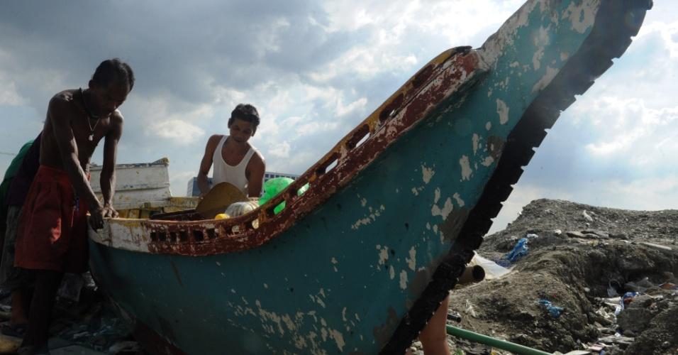 7.nov.2013 - Pescadores arrastam barco na costa da baía de Manila, enquanto o tufão Haiyan se aproxima, nesta quinta-feira (7). Autoridades alertam mais de 12 milhões de pessoas sobre os riscos do fenômeno climático, que deve alcançar ventos de mais de 330 km/h quando chegar à costa nesta sexta