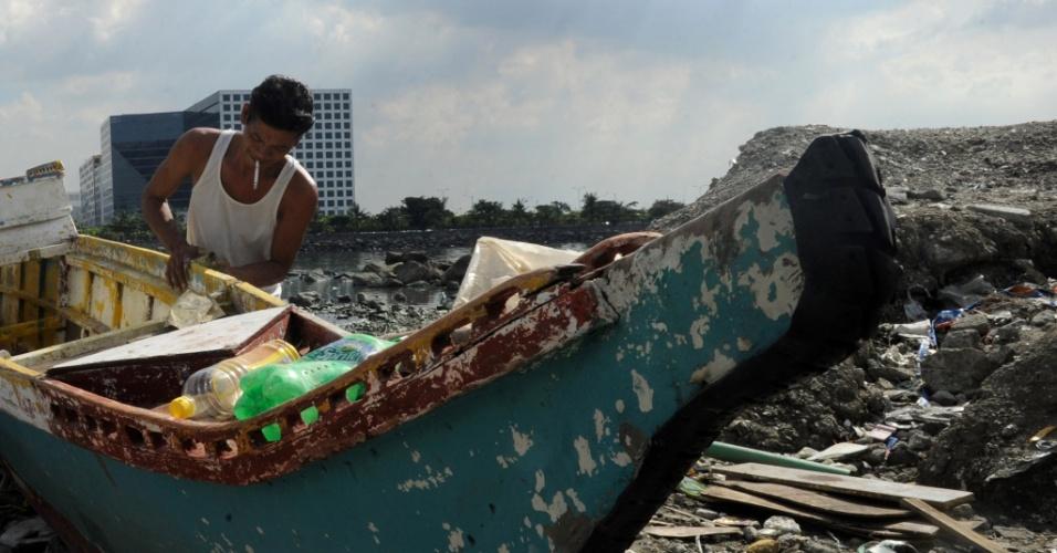 7.nov.2013 - Um pescador arrasta seu barco na costa da baía de Manila, enquanto o tufão Haiyan se aproxima, nesta quinta-feira (7). Autoridades alertam mais de 12 milhões de pessoas sobre os riscos do fenômeno climático, que deve alcançar ventos de mais de 330 km/h quando chegar à costa nesta sexta