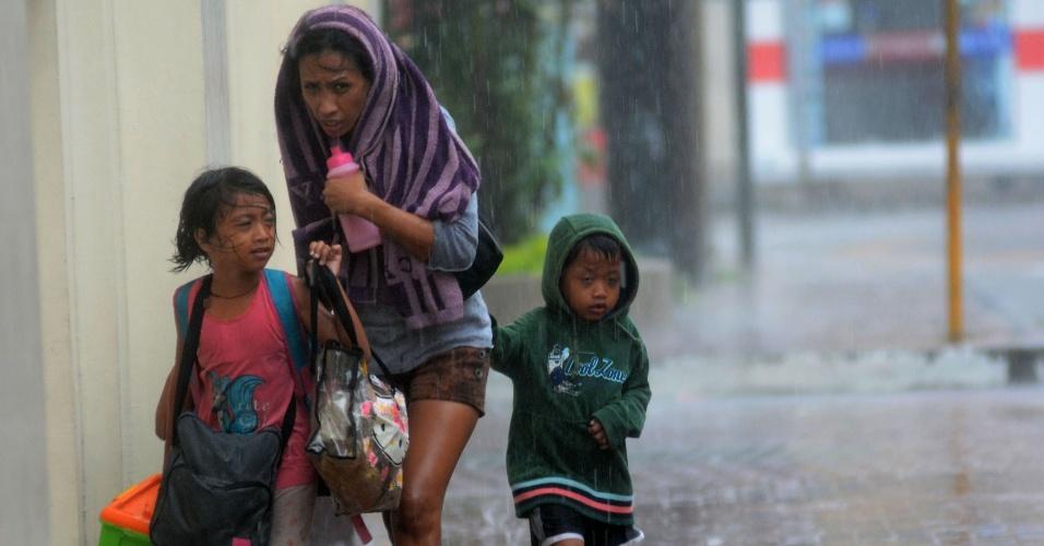 8.nov.2013 - Mãe e filhos enfrentam forte chuva a caminho de um centro de evacuação na cidade de Cebu, nas Filipinas, onde moradores da região tentam se proteger do tufão Haiyan, nesta sexta-feira (8).