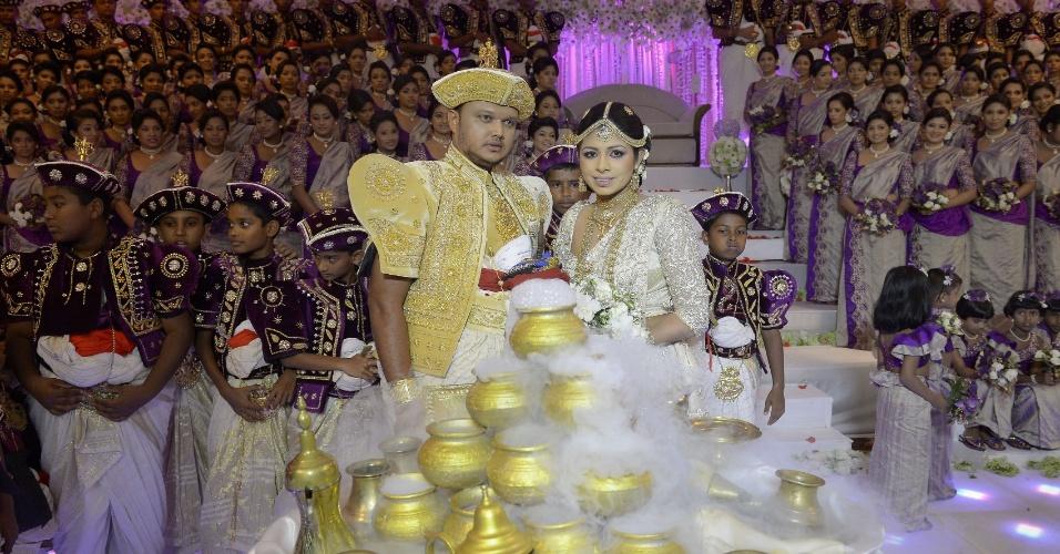 8.nov.2013 - O casal Nisansala (à direita) e Nalin posa para foto durante seu casamento em Negombo, no Sri Lanka. Com 126 madrinhas e 25 padrinhos, o casamento entrou para o Guinness Book, o livro dos recordes, como a cerimônia com mais madrinhas e padrinhos do mundo. O recorde anterior pertencia a um casamento em Bancoc, com 96 madrinhas