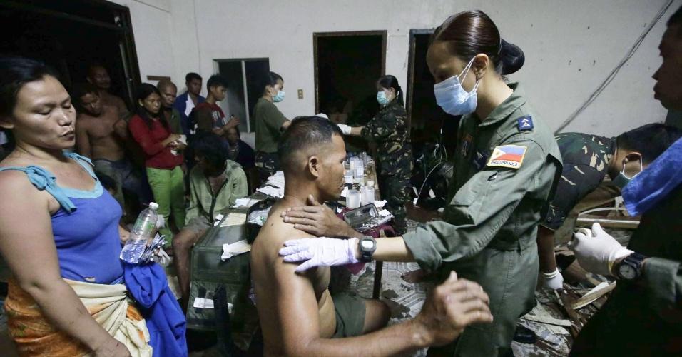 9.nov.2013 - Médicos do Exército filipino atendem vítimas do tufão Haiyan, na cidade de Tacloban, neste sábado (9). Considerada por especialistas como a tempestade mais forte da história, o tufão já matou centenas de pessoas no país e deixou rastro de destruição
