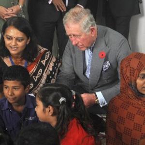 O príncipe britânico Charles (segundo à esq.) e sua mulher, Camilla (terceira à dir.), cumprimentam crianças indianas durante visita a uma creche em Mumbai