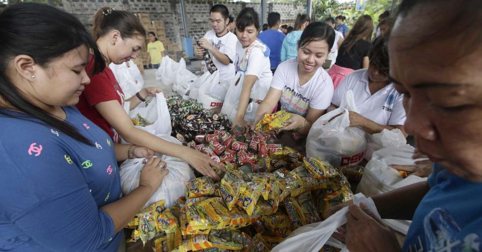 9.nov.2013 - Voluntários filipinos entregam cestas de comida em Manila, capital do país, após a passagem do tufão Haiyan, que deixou ao menos 1.200 mortos e milhares de desabrigados