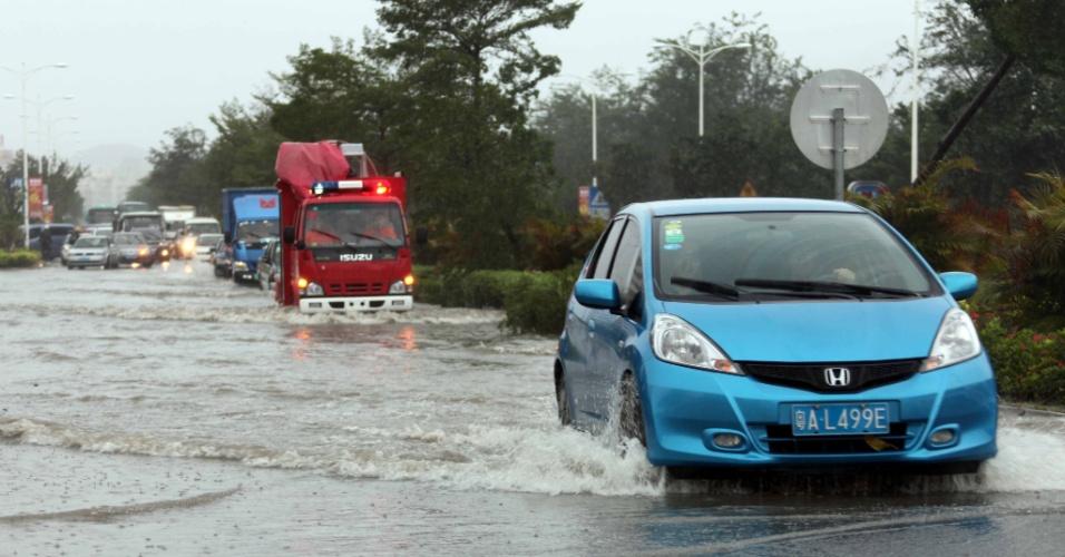 10.nov.2013 - Carro passa em estrada alagada com a aproximação do tufão Haiyan, da cidade de Sanya, no sul da província chinesa de Hainan