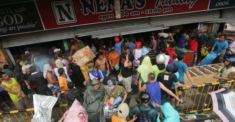 10.nov.2013 - Filipinos saqueiam loja de mantimentos após passagem do supertufão Hayan, na cidade de Tacloban, província de Leyte. A tempestade, uma das mais fortes já registradas, matou ao menos 10 mil pessoas no local, segundo a polícia