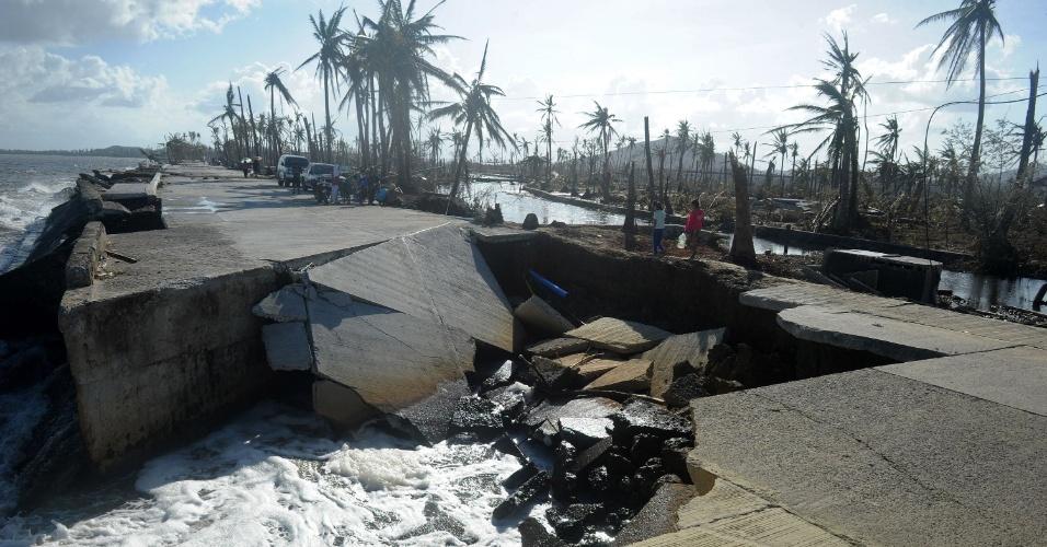 10,nov.2013 - Moradores caminham por via parcialmente destruída em Palo, nas Filipinas, após a passagem do super tufão Haiyan. As autoridades calculam que o número de mortos pode somar dez mil mortos