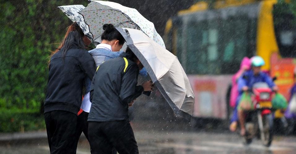 10.nov.2013 - Moradores tentam se proteger da chuva com vento forte causados pela aproximação do tufão Haiyan, da cidade de Sanya, no sul da província chinesa de Hainan