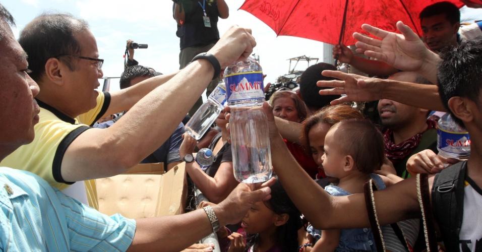 10.nov.2013 - O presidente filipino, Benigno Aquino (esq.), distribui kits humanitários às vítimas do tufão Haiyan, na cidade de Leyte
