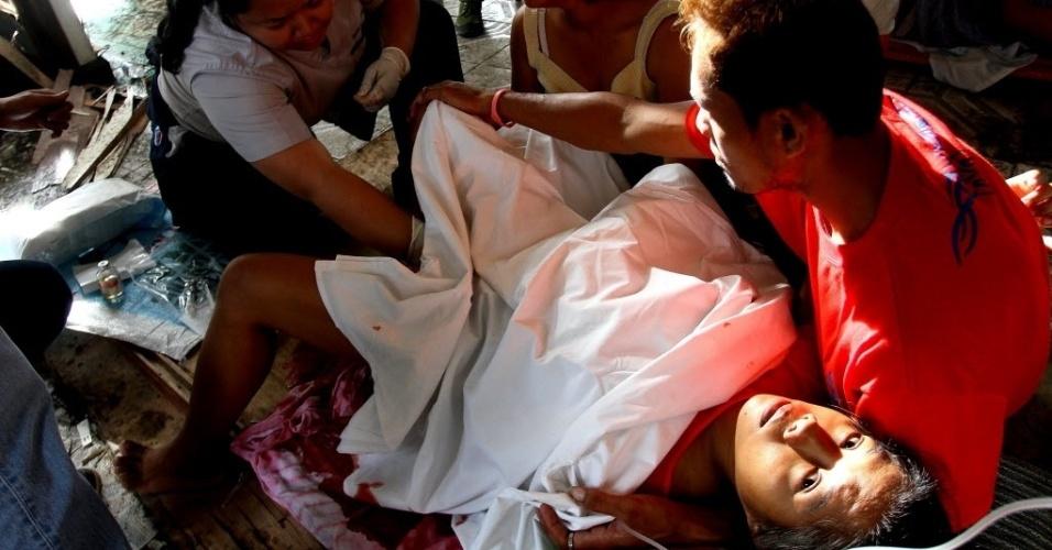 11.nov.2013 - Emily Sagalis, 21, entra em trabalho de parto deitada em piso de madeira de centro médico improvisado na cidade de Tacloban, nas Filipinas, atingida pelo tufão Haiyan desde sexta-feira (8). Emily deu à luz a menina Beatriz Joy