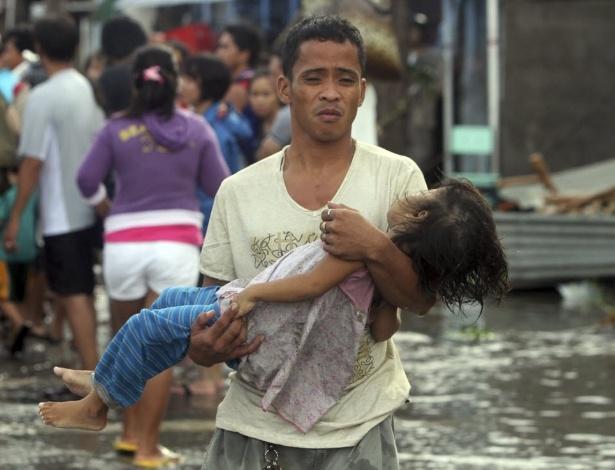 11.nov.2013 - Pai carrega corpo de filha nos braços a caminho de necrotério na cidade de Tacloban, nas Filipinas, devastada pelo tufão Haiyan. Na rua principal da cidade, de cerca 280 mil habitantes antes da tragédia, dezenas de corpos se decompõe a céu aberto. Três dias após a passagem do tufão Haiyan, ainda não foram enterrados