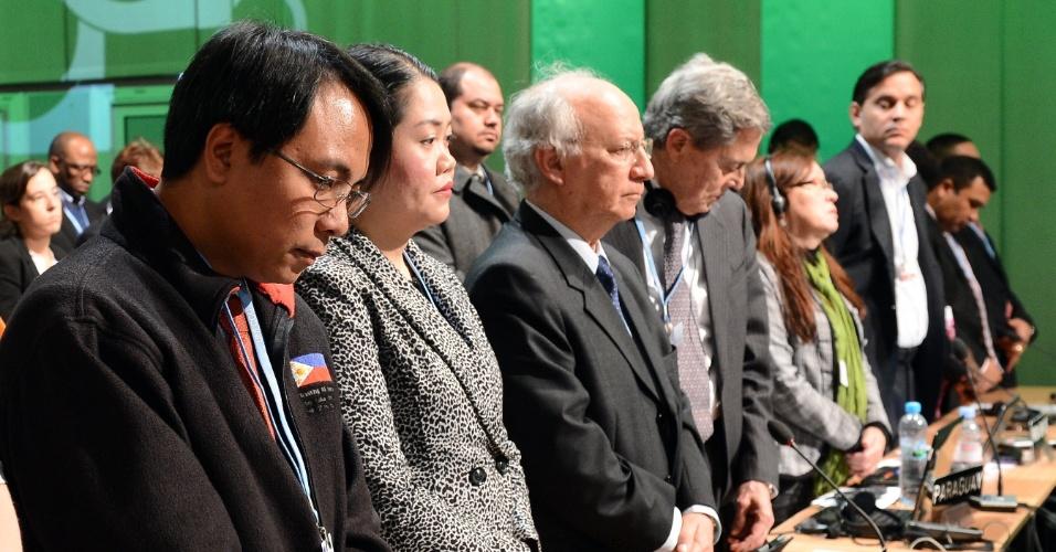 11.nov.2013 - Representantes da delegação filipina durante a Conferência do Clima da ONU, a COP-19, prestam homenagem às vítimas do tufão Hayian durante a abertura do encontro nesta segunda-feira (11), em Varsóvia, na Polônia
