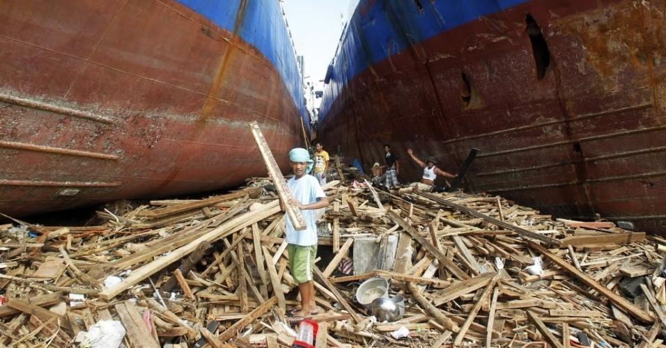 11.nov.2013 - Sobreviventes do tufão Haiyan pegam peças de madeira entre navios cargueiros em Tacloban, nas Filipinas, atingida pelo tufão Haiyan desde sexta-feira (8). Autoridades estimam que ao menos 10 mil filipinos morreram no desastre natural
