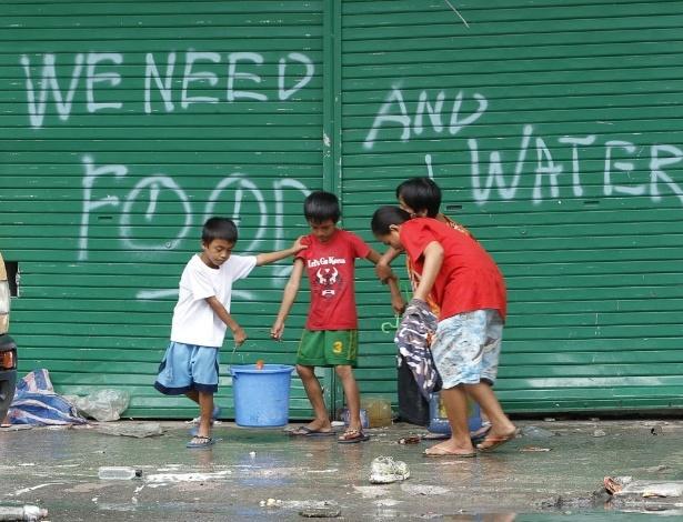 12.nov.2013 - Crianças ajudam a carregar baldes em frente a uma pichação com um pedido de água, na cidade de Tacloban, Filipinas
