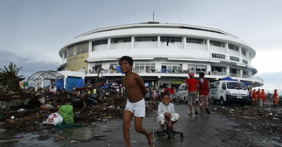 12.nov.2013 - Crianças brincam do lado de fora do Centro de Convenções de Tacloban, que se tornou um centro de refúgio improvisado para as pessoas deslocadas após a passagem do tufão Haiyan, nas Filipinas