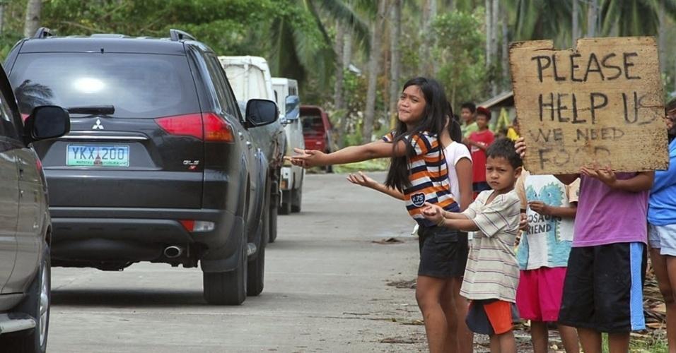 """12.nov.2013 - Crianças pedem ajuda para carros que passam por estrada de Cebu nas Filipinas. Pelo menos 1.744 pessoas morreram nas Filipinas durante a passagem do tufão """"Haiyan"""", informaram nesta terça-feira (12) os órgãos oficiais do país"""