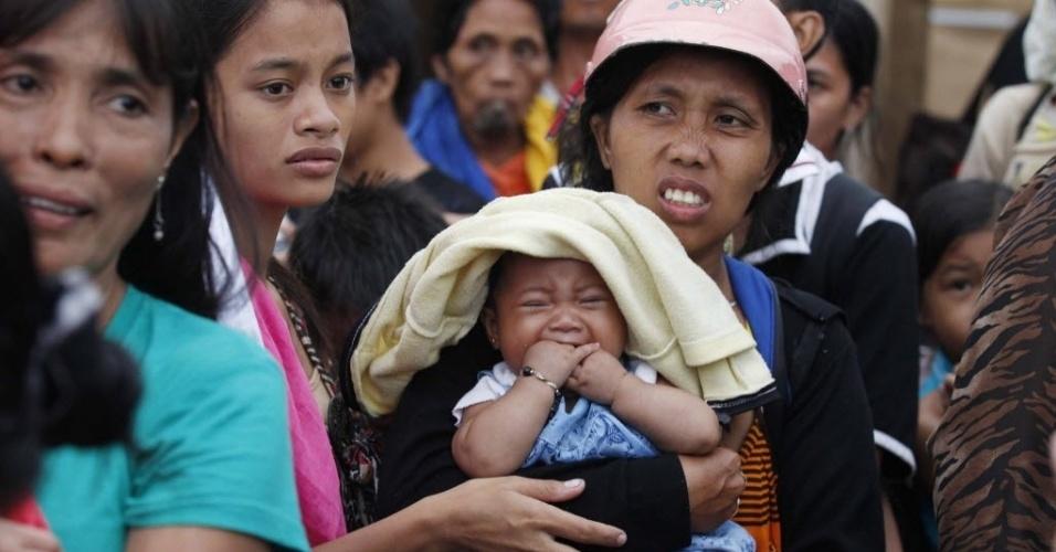 12.nov.2013 - Filipinos aguardam avião militar de resgate a cidade devastada de Tacloban, na província de Leyte, nas Filipinas
