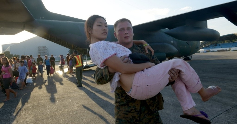 12.nov.2013 - Fuzileiro naval dos EUA carrega uma mulher ferida que sobreviveu a passagem do tufão Haiyan na cidade de Tacloban, Filipinas. A ONU pediu nesta terça-feira (12) US$ 301 milhões em ajuda humanitária para os filipinos afetados pelo tufão Haiyan, que teria matado ao menos 10.000 pessoas