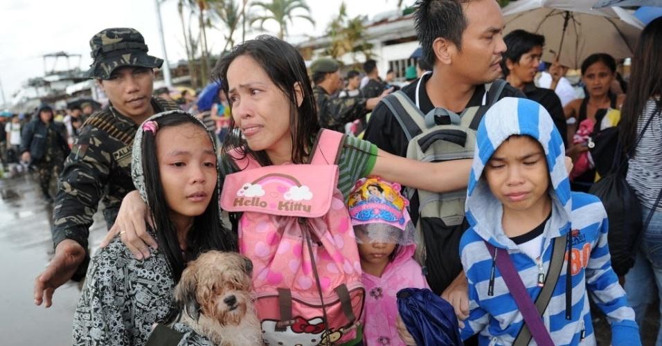 12.nov.2013 - Mãe chora após não conseguir embarcar com os filhos em um voo de resgate militar em Tacloban, na província de Leyte, região central das Filipinas
