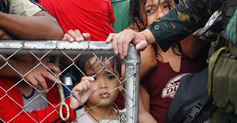 12.nov.2013 - Militares filipinos controlam portão de aeroporto em Tacloban, onde milhares de sobreviventes da passagem do tufão Haiyan procuram voos para deixar a cidade, que enfrenta falta de água e comida