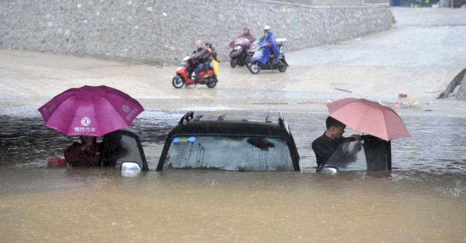 12.nov.2013 - Pessoas tentam retirar um carro de túnel inundado em meio a fortes chuvas derivadas do tufão Haiyan em Nanning, na região autônoma de Guangxi Zhuang, China. Pelo menos 12 pessoas morreram e outras 12 continuam desaparecidas após a passagem do tufão pela China