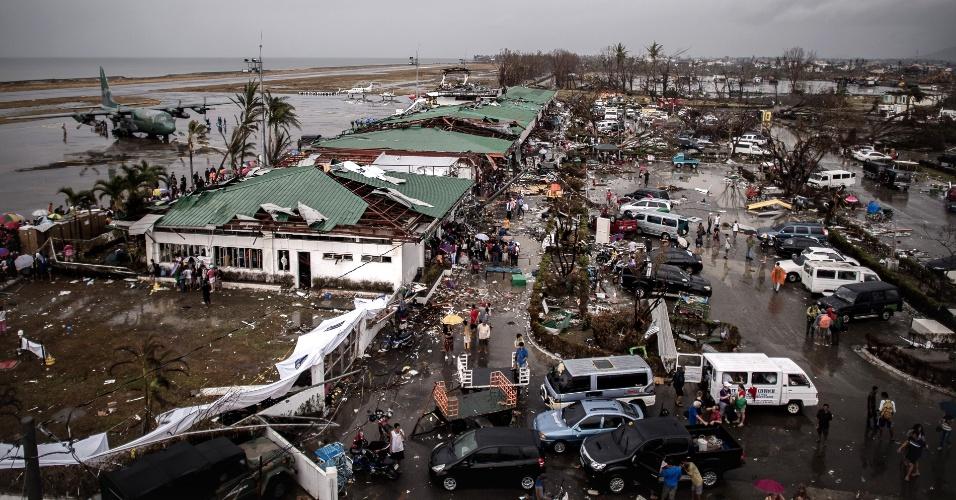 12.nov.2013 - Região do aeroporto de Tacloban, região central das Filipinas, fica cheia de destroços durante operação de evacuação da cidade, comandada por militares filipinos com o auxílio de aviões de carga e transporte, como o C-130, estacionado na pista. O tufão Haiyan, uma das mais fortes tempestades da história, destruiu cidades inteiras no país insular, causando mais de 10.000 mortes. Em Tacloban, estima-se que 5% das cerca de 200 mil pessoas tenham morrido na passagem do tufão