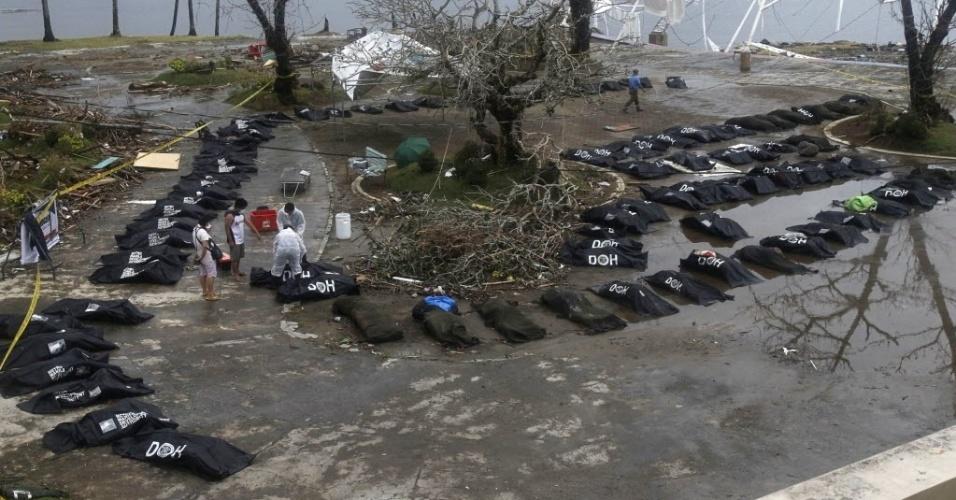 12.nov.2013 - Sobreviventes observam sacos com corpos de vítimas do tufão Haiyan na cidade de Tacloban, nas Filipinas, nesta terça-feira (12). Equipes de resgate tentaram chegar em locais isolados. Segundo autoridades, o número de mortos, que passa de 10 mim, pode aumentar rapidamente com a intensificação dos esforços nas buscas por vítimas