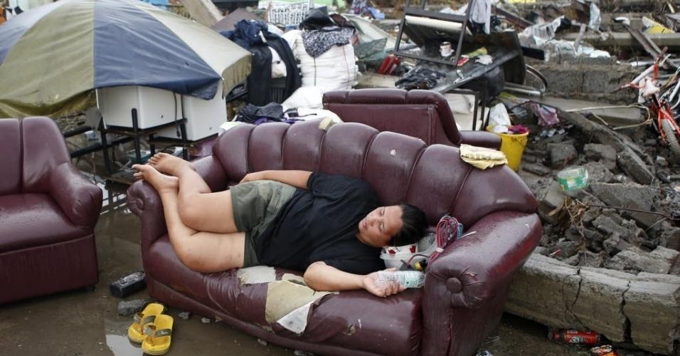 12.nov.2013 - Vítima do tufão Haiyan descansa em um sofá nas ruínas da casa de sua família em Palo, na província de Leyte, nas Filipinas. A ONU pediu nesta terça-feira (12) US$ 301 milhões em ajuda humanitária para os filipinos afetados pelo tufão Haiyan, que teria matado ao menos 10.000 pessoas