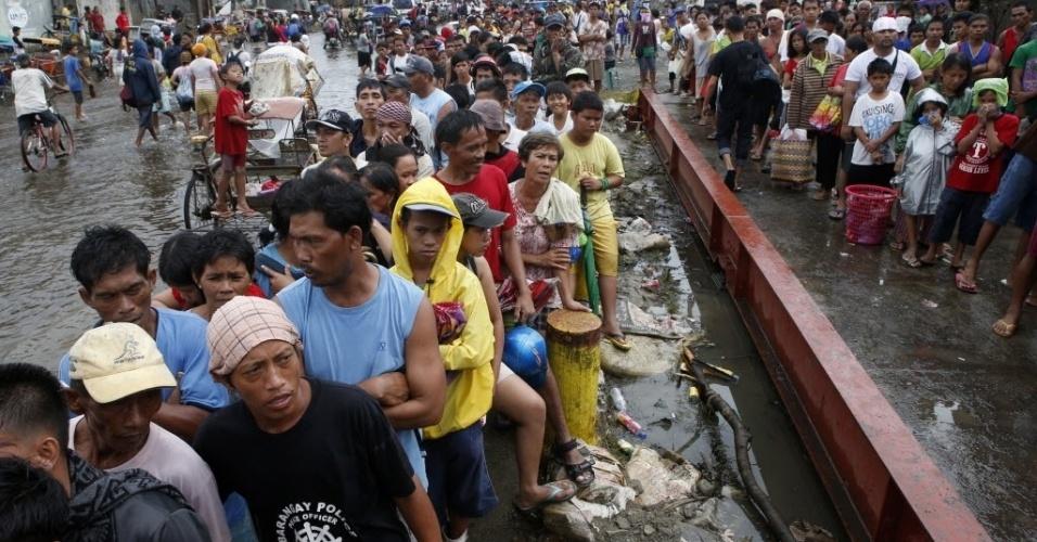 12.nov.2013 - Vítimas do tufão Haiyan fazem fila para conseguir arriz em um armazém nas Filipinas. As equipes de emergência e resgate trabalham para ajudar às vítimas e nas buscas por possíveis sobreviventes
