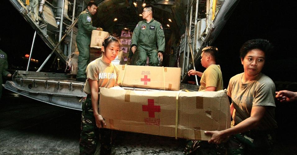 13.nov.2013 - Soldados das Filipinas e de Taiwan descarregam aeronave militar lotada de mantimentos que serão entregues às vítimas da passagem do tufão Haiyan no aeroporto internacional de Mactan-Cebu (Filipinas)