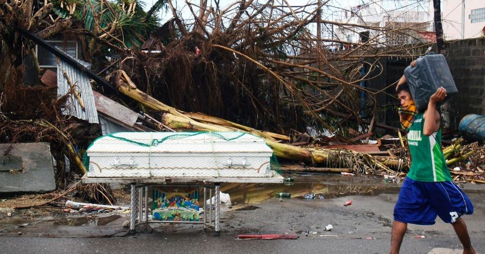 13.nov.2013 - Transeunte passa por caixão abandonado em rua destruída pela passagem do tufão Haiyan pela cidade de Tacloban