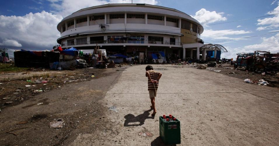14.nov.2013 - Garoto leva garrafas de água para centro de convenções que foi transformado em abrigo temporário após passagem de tufão, em Tacloban (Filipinas)