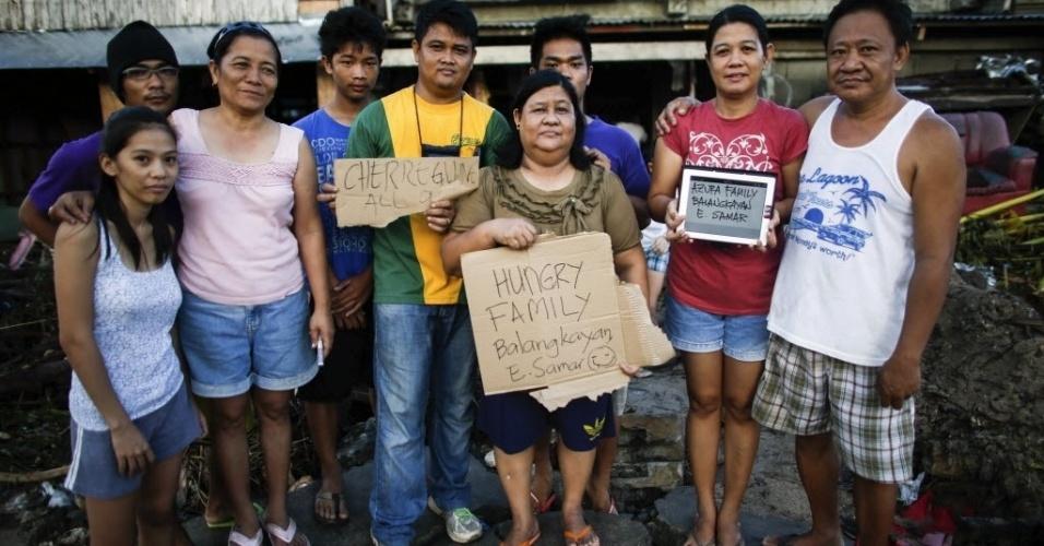 14.nov.2013 - Grupo de sobreviventes do tufão Haiyan exibem os nomes e pedem comida por meio de um tablet na província de Samar, nas Filipinas.  O fotógrafo John Javellana foi convidado por sobreviventes a postar fotos em redes sociais para identifica-los e dizer a parentes que eles estão vivos