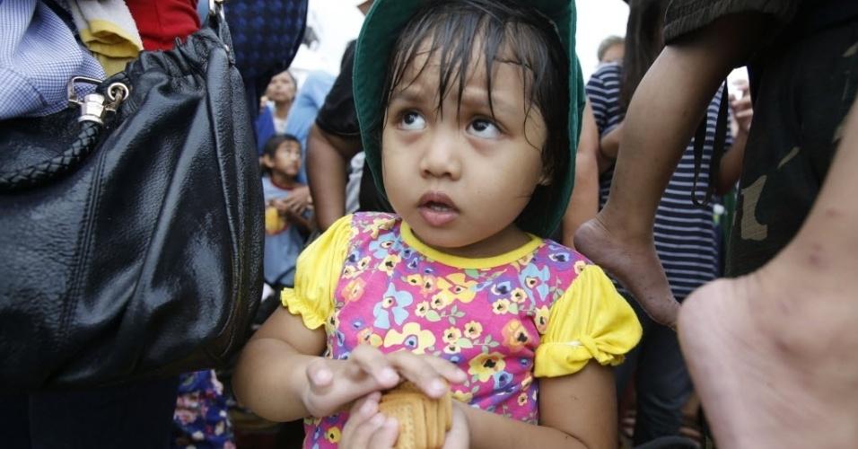 14.nov.2013 - Menina olha para cima depois de receber biscoitos do Programa Alimentar Mundial, das Nações Unidas, enquanto espera com os parentes para ser levada de Tacloban a Manila, Filipinas