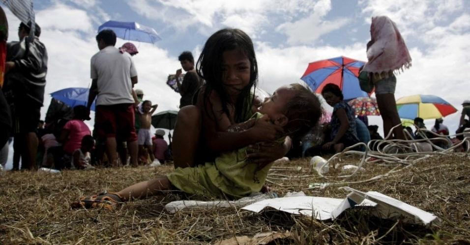 14.nov.2013 - Menina segura o irmão enquanto aguarda para embarcar em um avião em Tacloban (Filipinas). Integrantes da organização humanitária Médicos Sem Fronteiras afirmaram que muitas vítimas do tufão Haiyan não têm recebido ajuda ainda devido a problemas logísticos