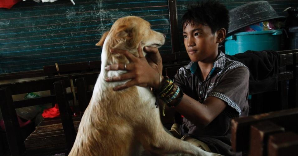 14.nov.2013 - Menino checa estado de saúde de cão em abrigo para sobreviventes do tufão Haiyan, em Tacloban (Filipinas). A ONU estima que 10 mil pessoas podem ter morrido apenas em Tacloban, atingida por ondas de até cinco metros