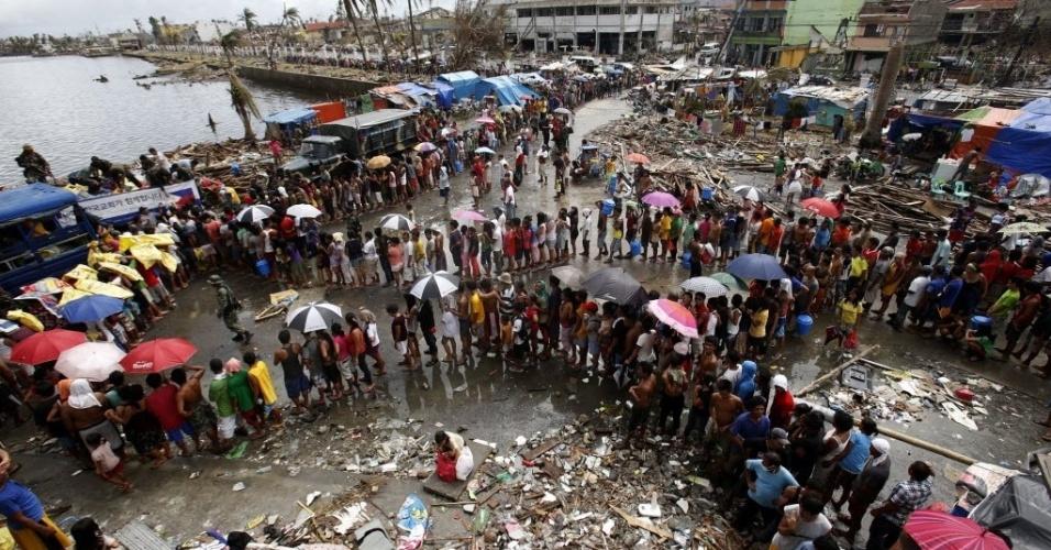 14.nov.2013 - Moradores de Tacloban aguardam em fila para receber água e comida, após passagem do tufão Haiyan, que devastou a cidade da região central das Filipinas