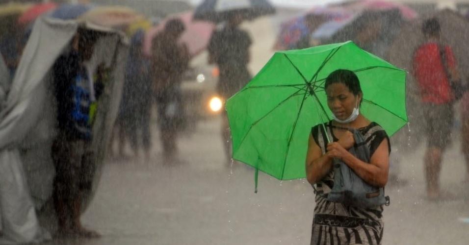 14.nov.2013 - Moradores de Tacloban enfrentam chuva forte enquanto esperam em fila para carregar as baterias de seus telefones celulares na prefeitura da cidade