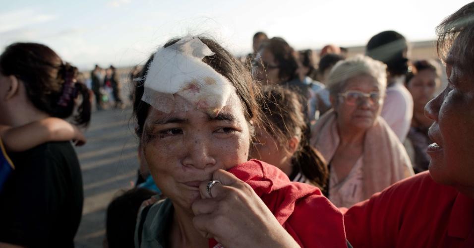 14.nov.2013 - Vítima da passagem do tufão Haiyan chora enquanto é evacuada por avião de carga do Exército no aeroporto de Tacloban (Filipinas). A ONU estima que 10 mil pessoas podem ter morrido apenas em Tacloban, atingida por ondas de até cinco metros