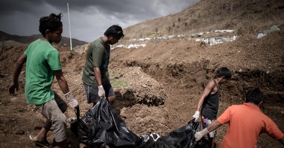 14.nov.2013 - Voluntários carregam corpos de vítimas do tufão Haiyan para uma vala comum nos arredores de Tacloban, Filipinas. Vários corpos, muitos deles não identificados, devem ser enterrados nesta quinta-feira (14)