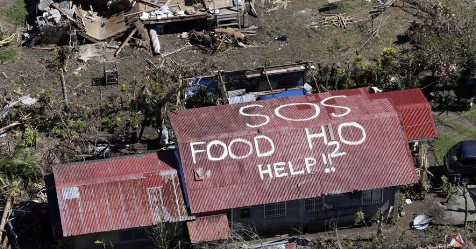 15.nov.2013 - Imagem aérea mostra um pedido de socorro escrito no telhado de uma casa na cidade de Tacloban, na Filipinas, nesta sexta-feira (15). Os moradores da localidade, uma das mais atingidas pelo tufão Haiyan, pedem água e comida