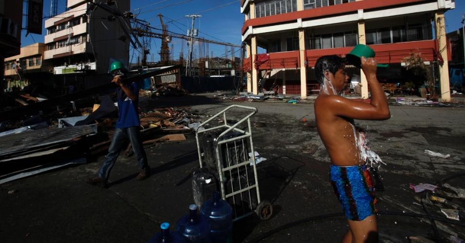 15.nov.2013 - Morador toma banho em rua de de Tacloban --a cidade mais afetada pelo tufão Haiyan, que devastou o país há uma semana-- com água retirada de tubulação subterrânea