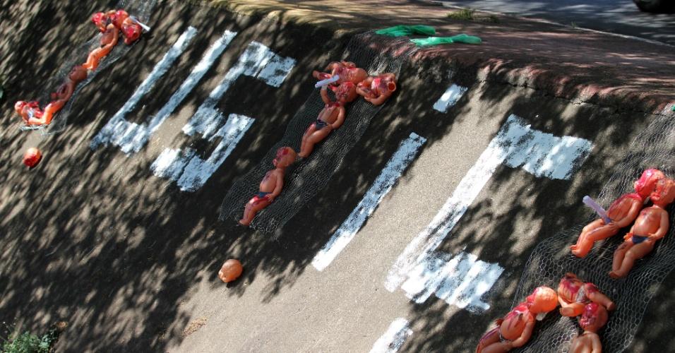 15.nov.2013 - Moradores pedem justiça no caso da morte do garoto Joaquim Ponte Marques, 3, em ato no córrego Retiro Saudoso, na avenida Francisco Junqueira, região central de Ribeirão Preto (SP). Os bonecos representam crianças vítimas de violência