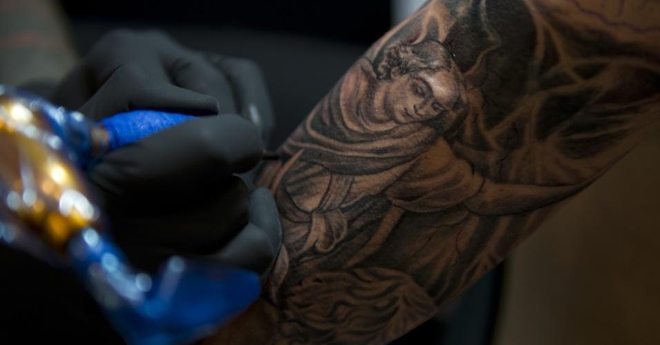 15.nov.2013 - Um tatuador desenha sobre o corpo de um cliente na Bogota Tattoo Convention, em Bogotá, nesta sexta-feira (15). Cerca de 300 tatuadores de todo o mundo apresentam a sua arte na sétima edição do evento, que acontece entre 15 e 17 de novembro, e também conta com apresentações de dança e uma feira de roupas